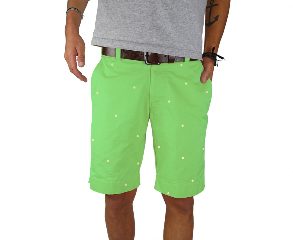 Front view man standing wearing green shorts with embroidered dots on them against white background - hand in pocket