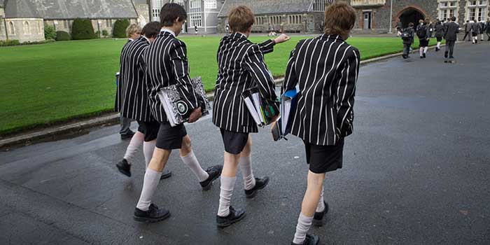 British school boys walking to class, carrying books while wearing shorts