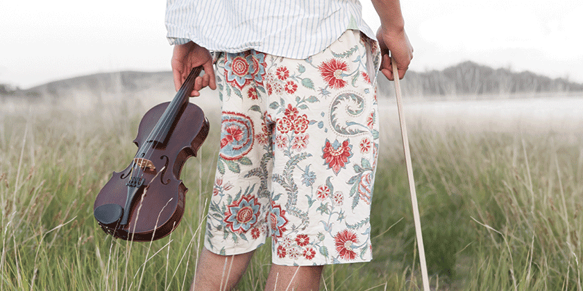 Man wearing shorts in a field holding a violin