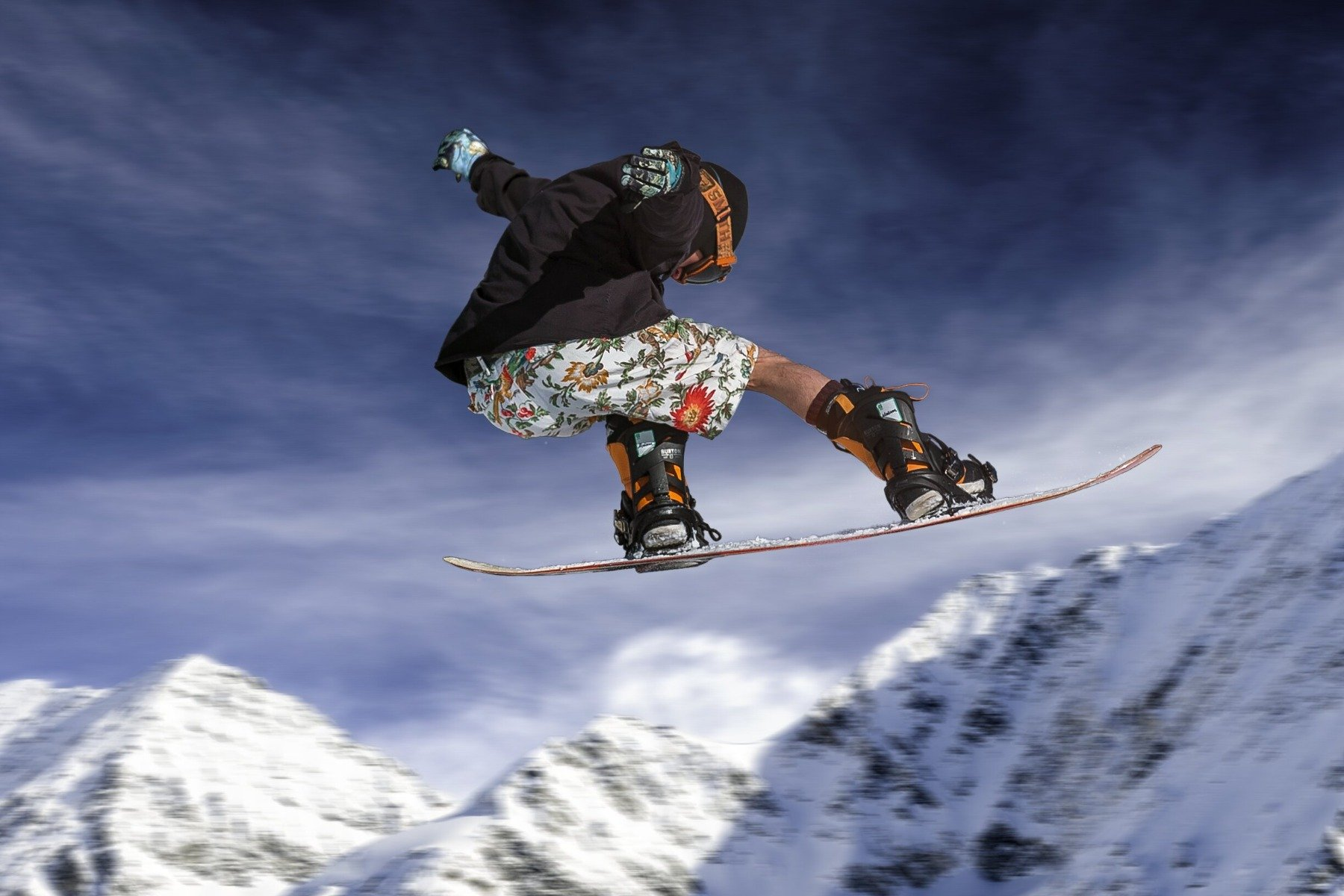 Man wearing floral shorts flying through air on snowboard